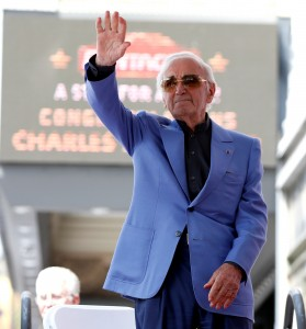 FILE PHOTO: Armenian-French singer Aznavour waves before unveiling his star on the Hollywood Walk of Fame in Los Angeles